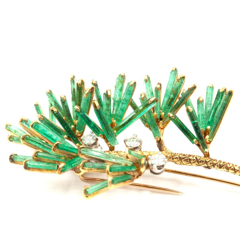 A 18K yellow gold, Emerald and Diamond brooch. The brooch is a true masterpiece with 49 natural rough Emerald stones set as branches, resembling leaves on a plant. Four natural round Diamonds approximately .90 Ct are set along the brooch giving this