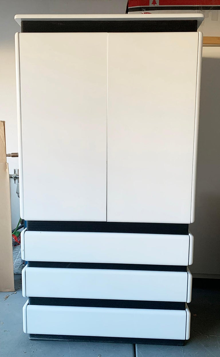 An absolutely stunning Postmodern highboy by Rougier. This highboy has clean white gloss with black accents and would look perfect in any modern, Mid-Century Modern, Space Age or Memphis style environment.   This highboy is in good condition with