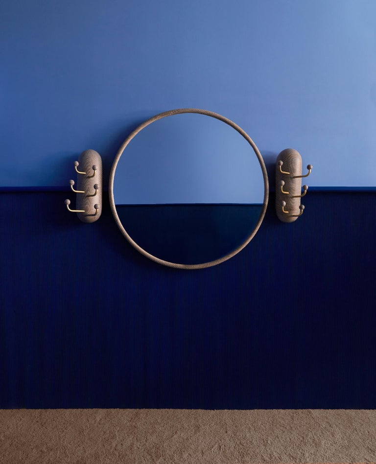 A carefully constructed ring produced from twelve pieces of wood create a clean but structurally complex profile. The tubular shape creates a smooth and sculptural surface with a recess at the back to allow the mirror to float off wall. The white