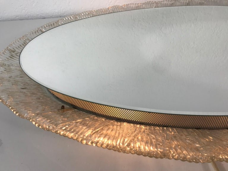 An illuminated wall mirror from the German manufacturer Hillebrand Lighting. It was made in the 1970s. The mirror has a oval acrylic design. There are E14 light bulbs inside the frame. The mirror is in a good vintage condition.