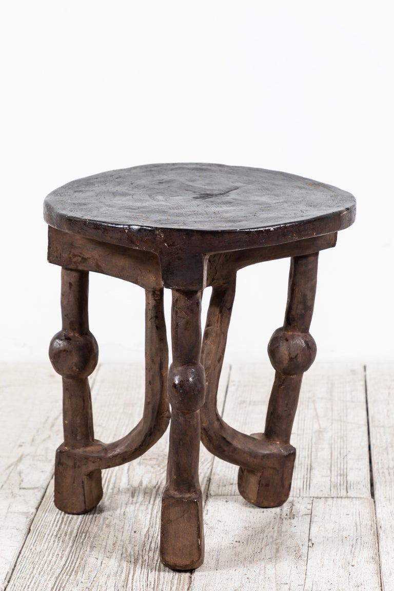 Solid round African stool with unique carvings.