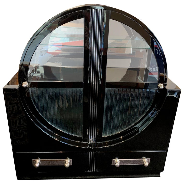 Extraordinary round Art Deco showcase vitrine  Black piano lacquer, high-gloss polished. Original glass windows.  Inside with 2 black wood plates and 1 glass plate. Upper half inside with mirror glass in the back Cannelured front with chrome
