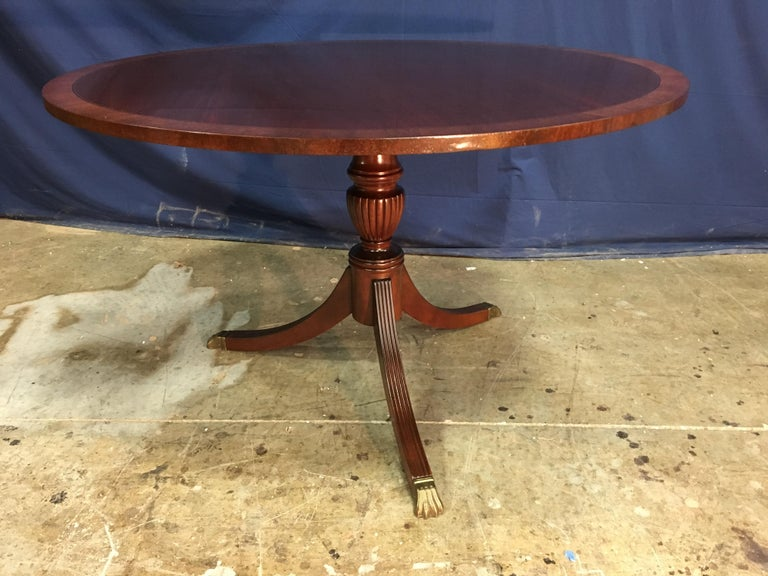 This is made-to-order round traditional mahogany accent/foyer table made in the Leighton Hall shop. It features a field of cathedral mahogany with a contrasting mahogany border. It has a hand rubbed and polished semigloss finish. The pedestal has