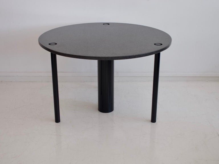Round table with black lacquered metal feet and granite top. Manufactured in Italy in the 1970s.