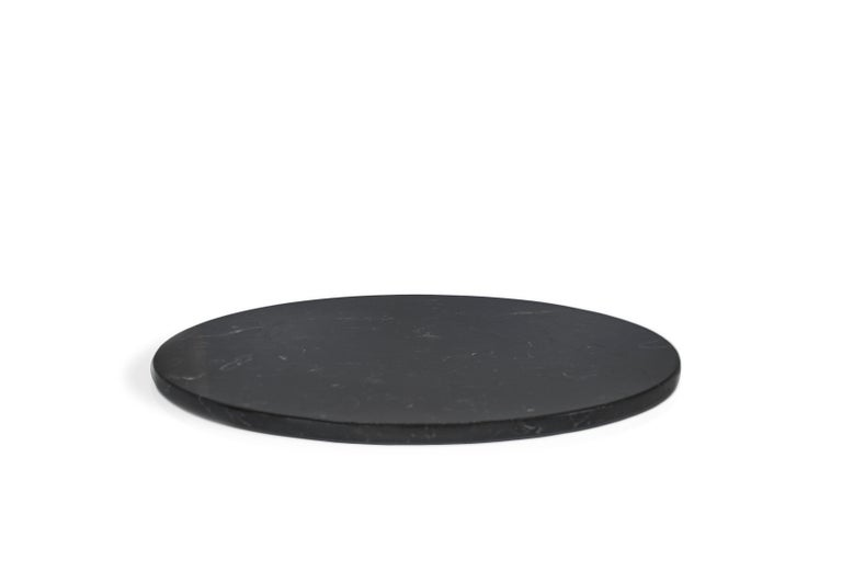 Rounded black marble cheese plate. Each piece is in a way unique (every marble block is different in veins and shades) and handmade by Italian artisans specialized over generations in processing marble. Slight variations in shape, color and size are