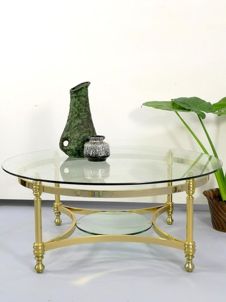 Round brass coffee table with glass top and shelf, 1970s.
