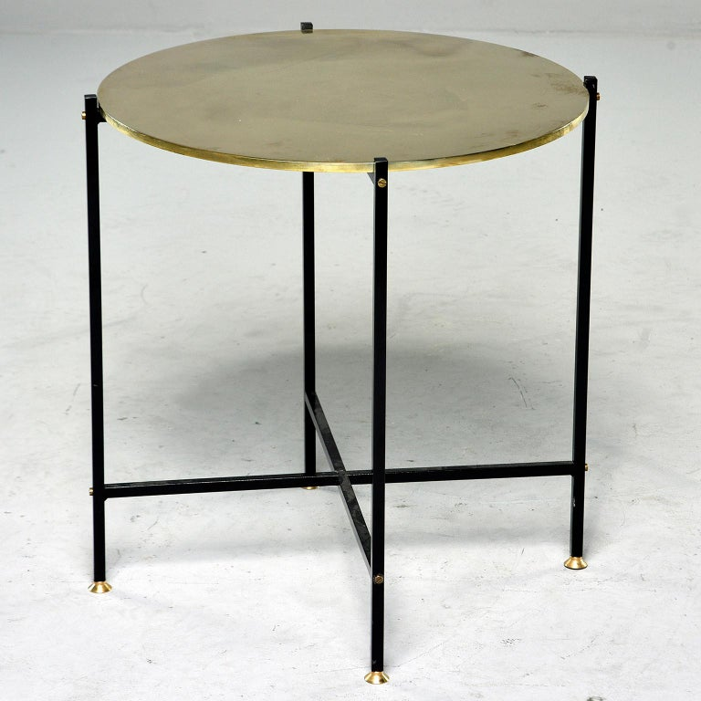 Contemporary side table found in Italy has round, polished brass top with slender black iron base with X-form stretcher and brass feet. Two available at time of this posting. Sold and priced individually.