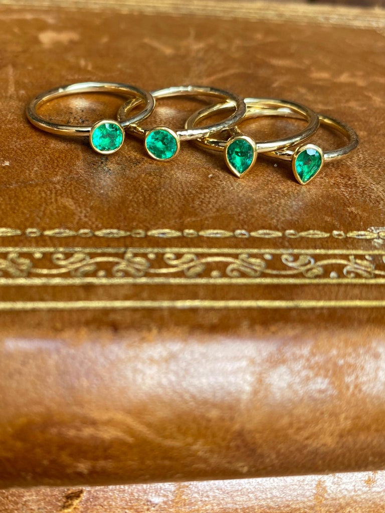 A clean and bright Colombian round brilliant emerald is featured in this hand forged stacking ring. It is crafted in 22 and 18 karat gold by our master goldsmith in California. The price as listed is for one ring.   -Colombian emerald round of 0.25