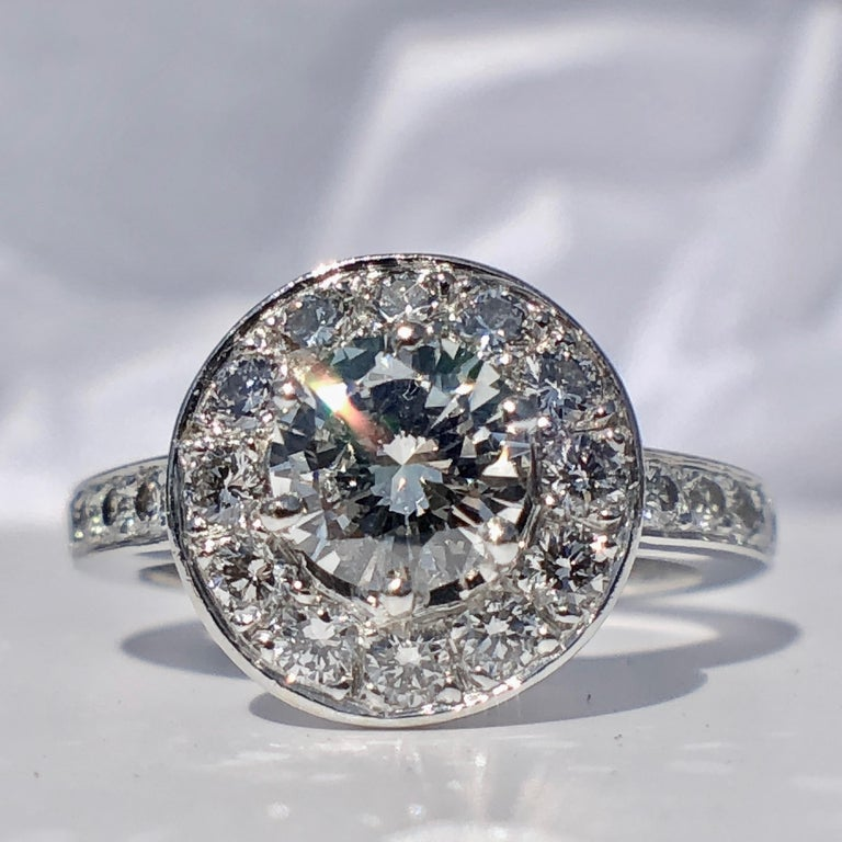 The central round brilliant cut white diamond dazzles with the most exceptional fire and sparkle, framed by more diamonds for the beautiful halo.  Simply stunning, this beautiful 18k white gold diamond halo ring is designed to sparkle. Inspired by