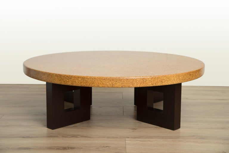 Mid-Century Modern round cork top coffee table with stained mahogany frame-shaped legs by Paul Frankl for Johnson Furniture. Model #5021, circa 1950. Newly refinished to mint condition.