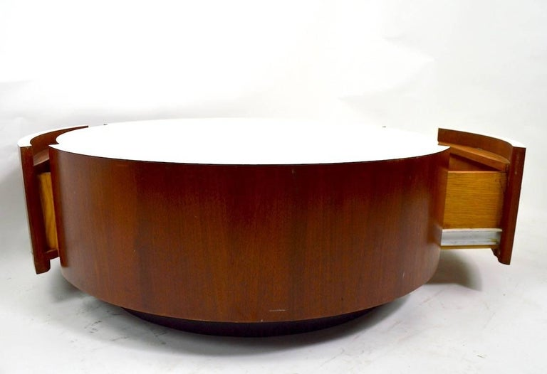 Disk form coffee table with textured white formic top, veneer sides, and two deep storage drawers. We believe this was a custom-made item, circa 1970s. This example shows some cosmetic wear, scuffing at the sides, normal and consistent with