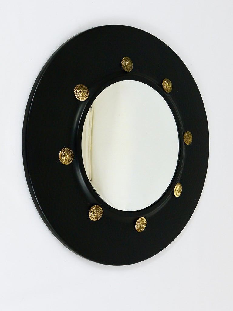 A very beautiful round wall mirror with convex mirror glass from the 1960s, made in Italy. In the style of Piero Fornasetti. The frame is made of black-finished