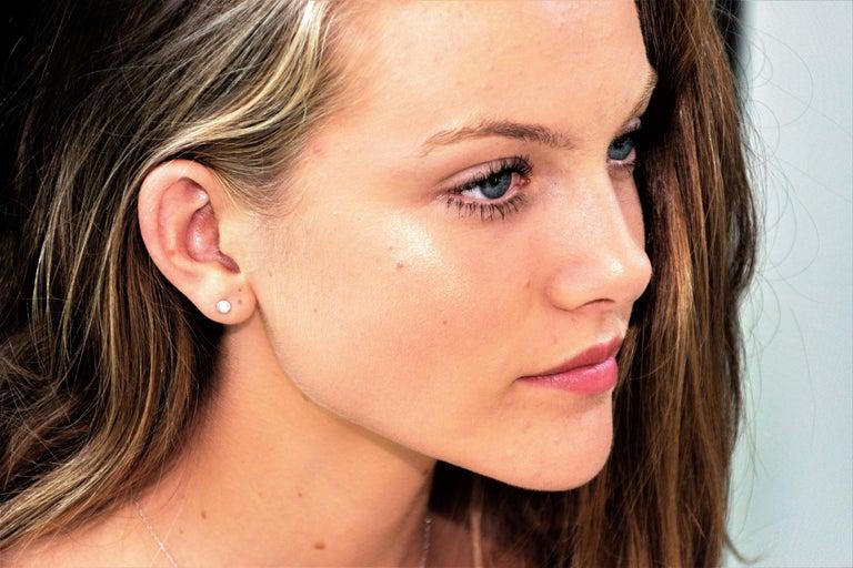 14k white gold bezel set stud earrings Round diamond weighing 0.24 carat  Width of the earrings 0.17