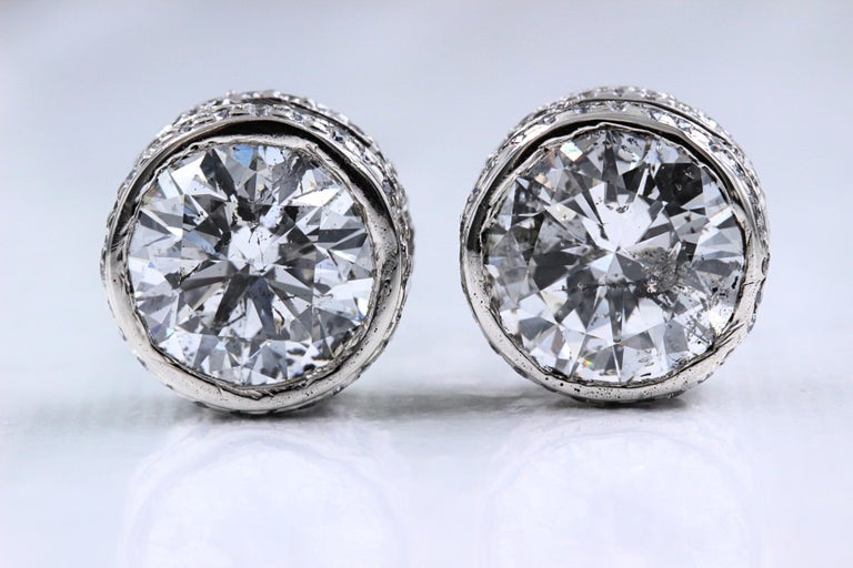 Round Diamond Solitaire Stud Bezel Set Earrings  Metal:  14k White Gold Width:  10.3 MM Width - 6.08 MM Height Total Carat Weight:  5.87 tcw Diamond #1:  Round 2.31 cts I color, I1 clarity   Diamond #2:  Round 2.38 cts I color, I1 clarity Accent