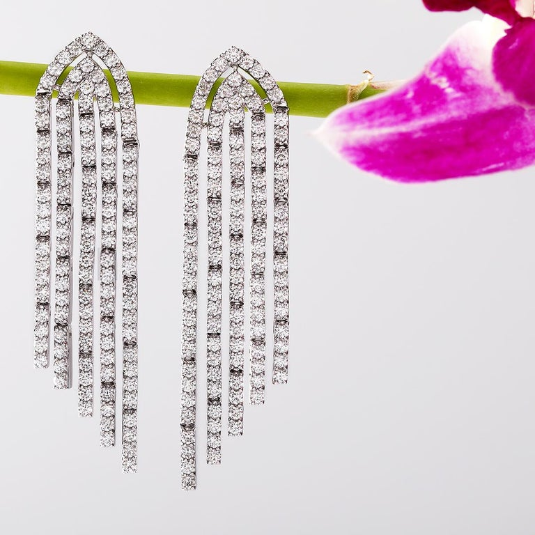 The stage is yours. Iconic because of its round cut diamonds, the lustre diamond earrings will instantly cast you under the spotlight.  Set in 18 kt white gold and IGI Certified.  IGI CERTIFIED  Gold- 14.74 gms Diamond- 3.34 carats Diamond Colour: