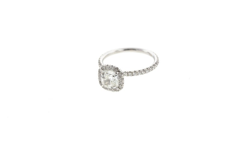This stunning round diamond engagement ring has a built-in (raised) setting and features a gorgeous diamond cushion-shaped halo and diamonds on the shank. It's one of our most popular style of ring and for a good reason: this classic engagement ring