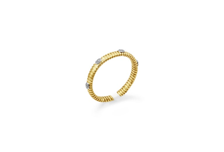 A fashionable flexible cuff bracelet in a chic spiral design made in 18k yellow gold. Accented with micro-pave of round brilliant diamonds weighing 0.37 carats total. Approximately 27.18 grams