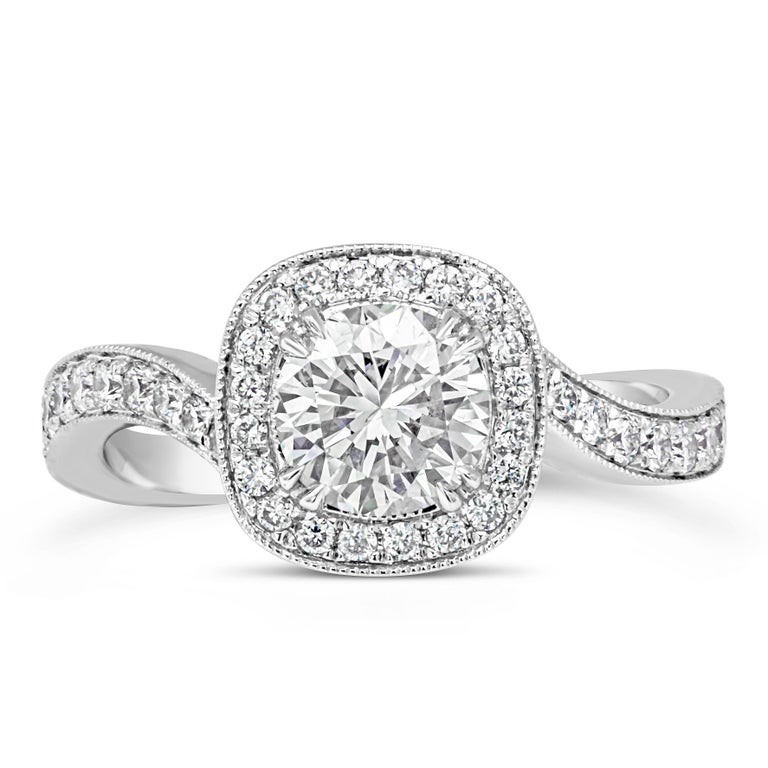 An unusual and intricately designed engagement ring and wedding band set. The engagement ring features a 0.98 carat round brilliant diamond center set in a diamond encrusted cushion halo finished with milgrain edges. The halo is attached to a wavy