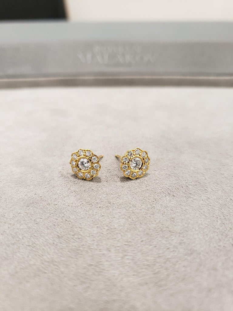 Each earring showcases a round brilliant diamond, surrounded by smaller round brilliant diamonds. Set in 18 karat yellow gold. Diamonds weigh 1.12 carats total.  Style available in different price ranges. Prices are based on your selection of the