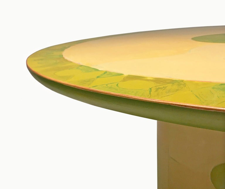 A unique, commissioned wooden dining centre table by artist and designer Randy Shull with a round, beveled top and a cylindrical base that has eight round plastic protective feet. The table is hand painted in approximately 50 layers, with sanding in