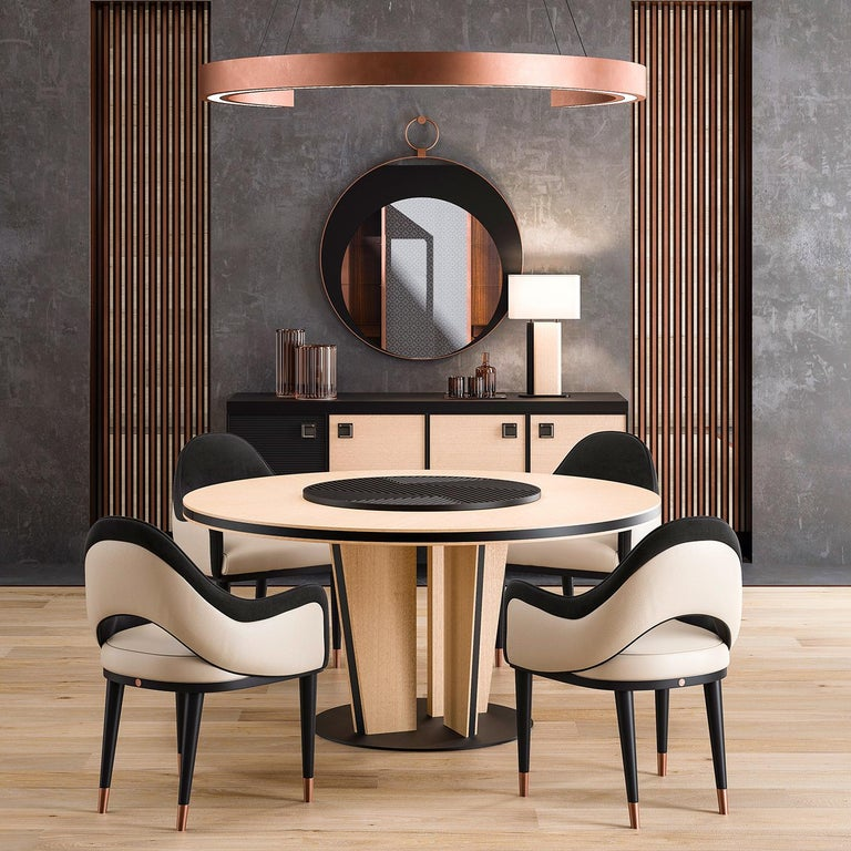 Marked by a two-tone design, this stunning round table is crafted on beige eucalyptus veneer with black-lacquered inserts. The base sits on a round black-finished metal plate and is made up of four legs set closer to the center to form a pillar-like