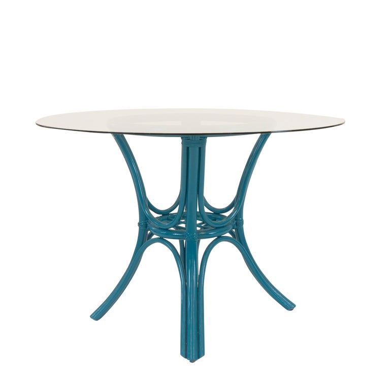 """A Classic outdoor dining table with a midcentury curved rattan base and glass top. The base features crisscross and woven details that are newly lacquered in blue.   The table cloth pictured is sold separately.  Measurements  29""""H x 42""""W."""
