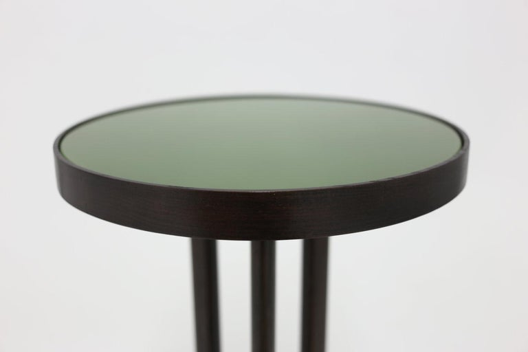 The Sutton side table shown with round green painted glass top and beautiful dark mahogany base - all hand carved and painted. Item is available