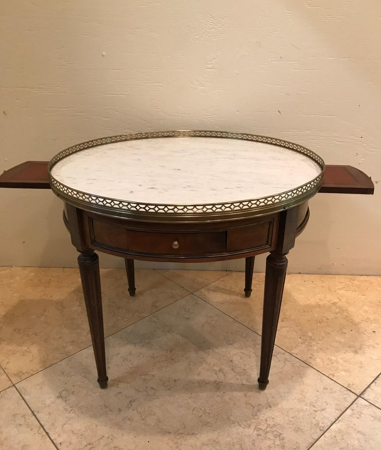 French Bouillotte cocktail table with two drawers and two pullout extensions. A brass gallery surrounds the marble top.