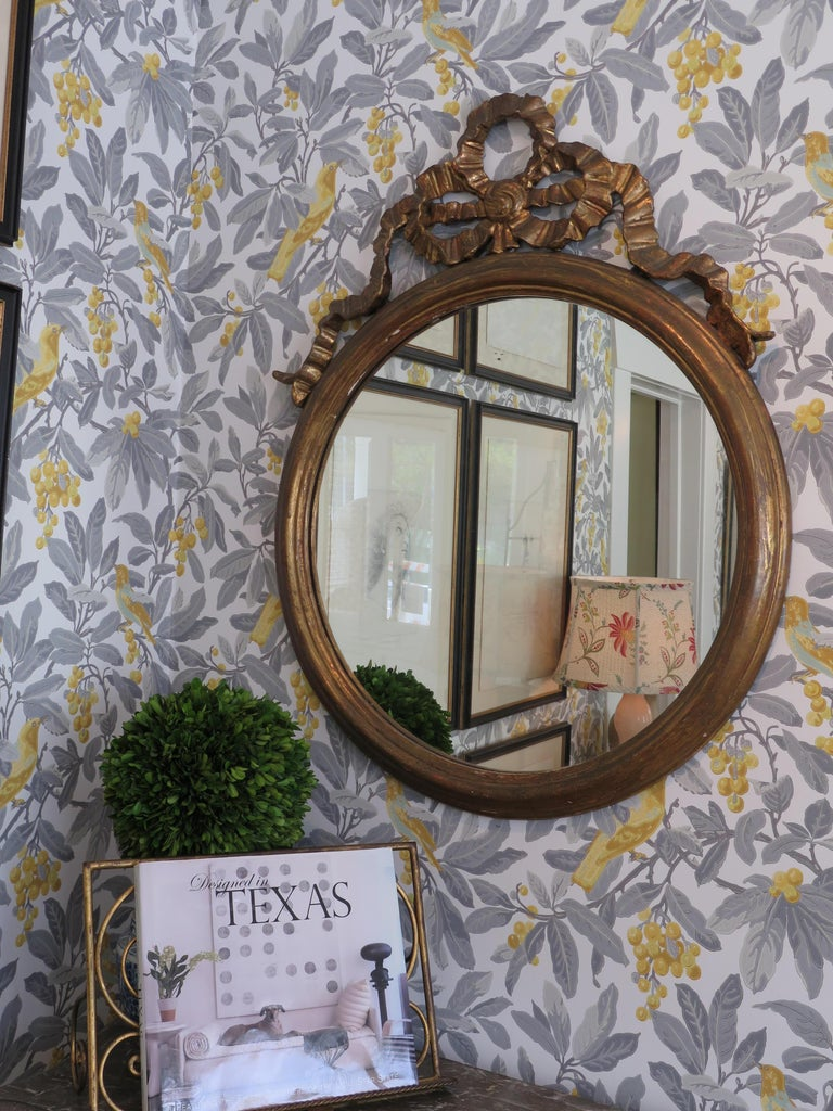 Round gilded mirror adorned with a large bow. Great addition to any space.