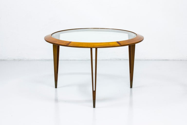 Round coffee table designed by Bertil Fridhagen. Produced in Sweden by Bodafors during the 1940s-1950s. Made from beech wood with contrasting inlays of mahogany in the circular frame. Glass top with etched line. Tapered legs with brass feet endings.