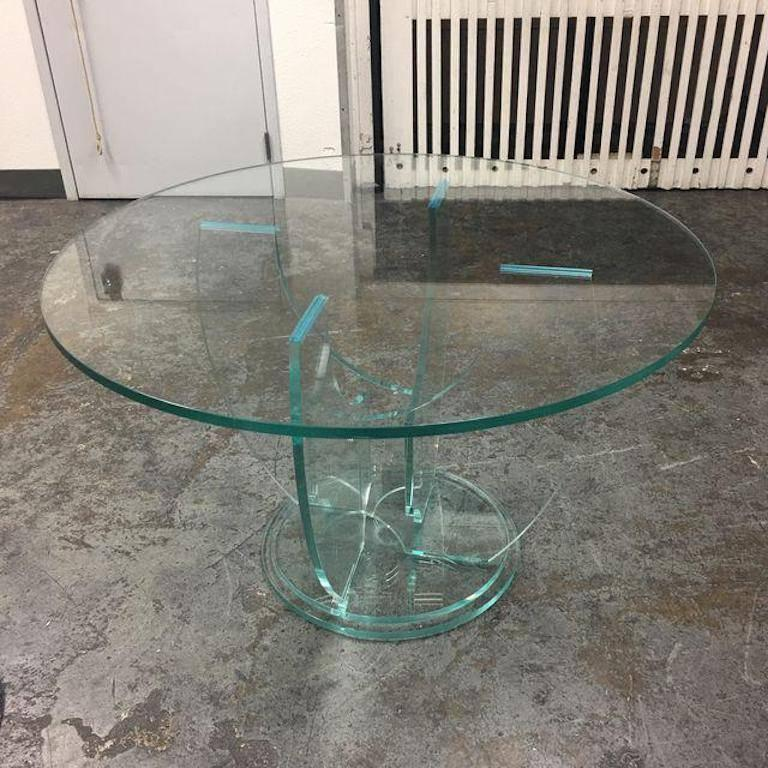 A Modern Glass Dining Table. A Round 48 Inch Glass Sits On A Four Glass