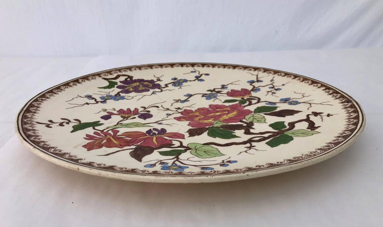 This is a beautiful round porcelain Imari platter with a hand painted floral design. The colors are vibrant pink, greens, brown, purple and blue. It has a small pedestal which gives the platter a built in lift for better presentation.