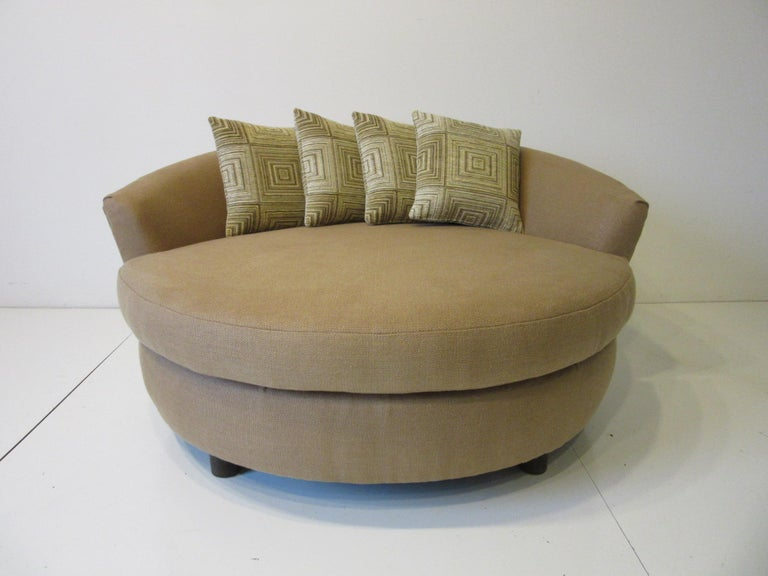 A round upholstered lounger / sofa chair with curved backrest all covered in soft and comfortable Italian linen with four woven fabric throw pillows. Sitting on larger rounded wooden legs making this piece very sturdy and useful for your living