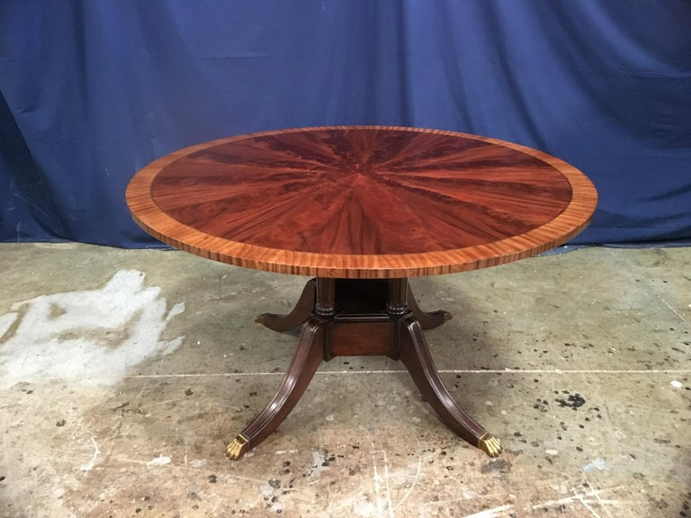 This is made-to-order round traditional mahogany dining table made in the Leighton Hall shop. It features field of radial cut West African swirly crotch mahogany and a border of satinwood. There is an inlay of ebony and white maple which separates