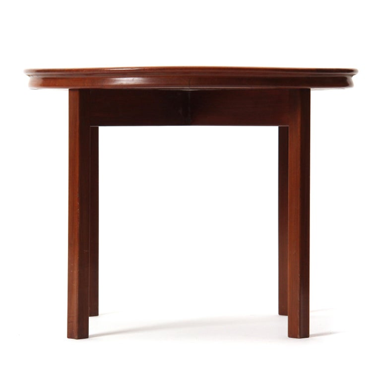 A round mahogany end table / side table attributed to Ole Wanscher featuring a flared rim and straight, concave-faced legs. Made in Denmark, circa 1940s.