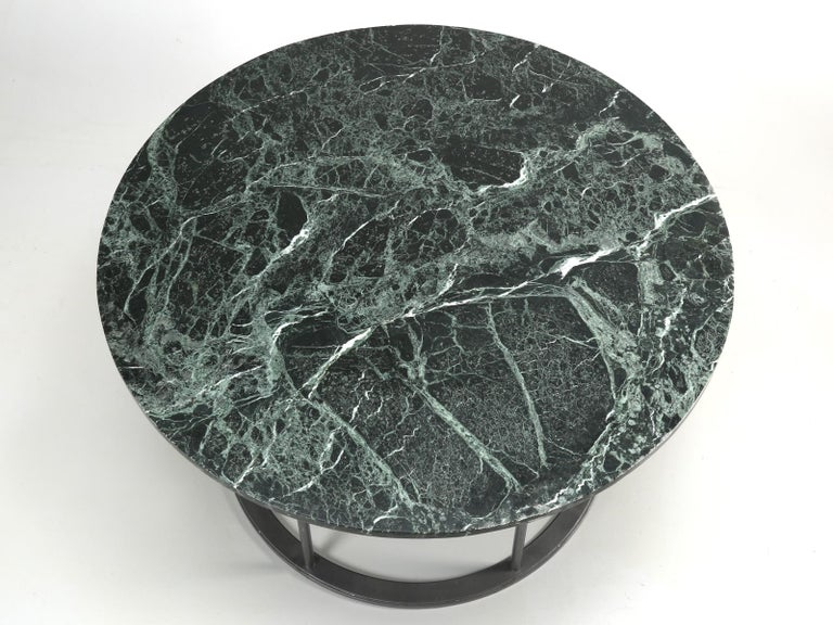 Round marble dining table with a strong painted circular steel base and can be used indoors or outdoors. The marble top came to us from France and the history of the steel base remains a mystery. This marble and steel dining table, will seat between