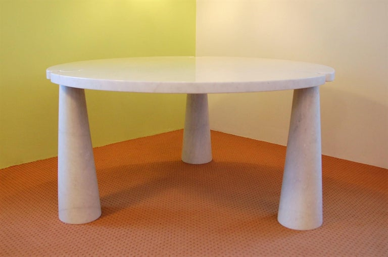This beautiful and elegant round marble dining table was designed by Angelo Mangiarotti for Skipper in 1971. It is made solely of white Carrara marble. The top slides over the three cone shaped legs which makes it a very solid construction. This