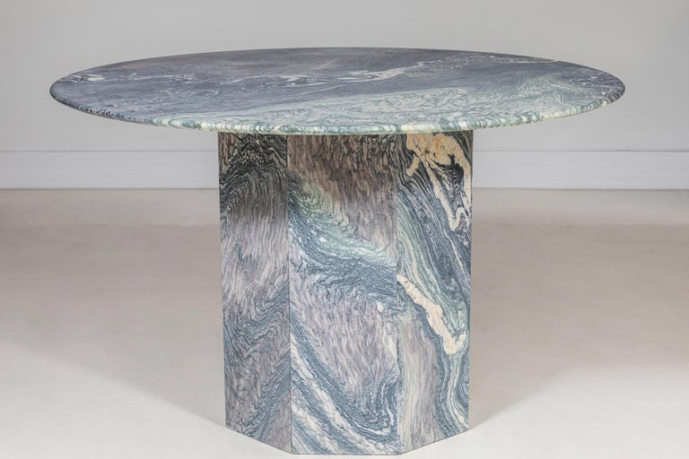 Round matte honed marble table with faceted pedestal base.