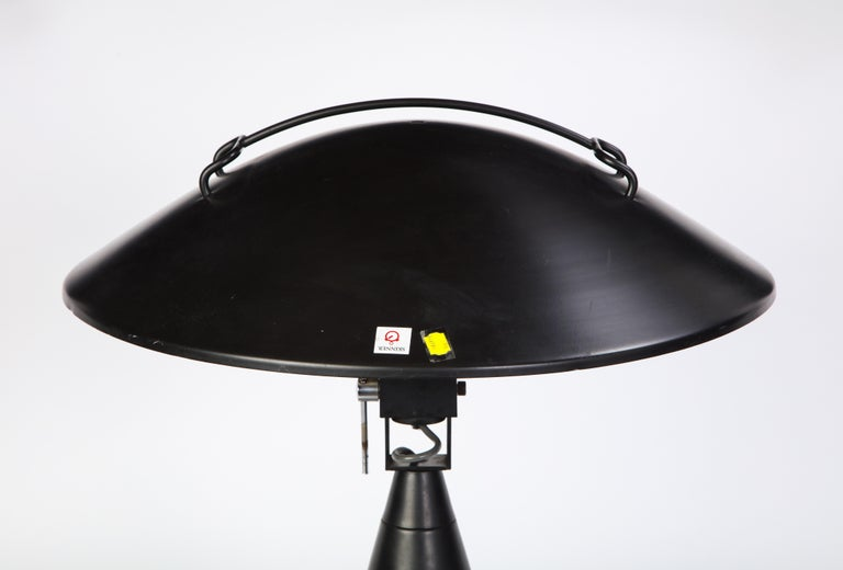 The shape of this modern black painted metal desk or table lamp is a discussion of the relationship between form and function. Showcasing an industrial, lantern-like design and a matte black finish, this piece will make a geometric statement in any