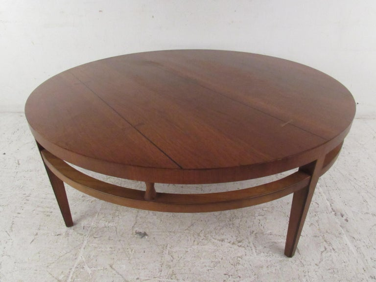 This stunning vintage modern coffee table boasts a circular shape with a stretcher wrapping all the way around. A sleek design with sculpted hourglass fixtures placed between the top and the stretcher. This handsome piece with a vintage walnut