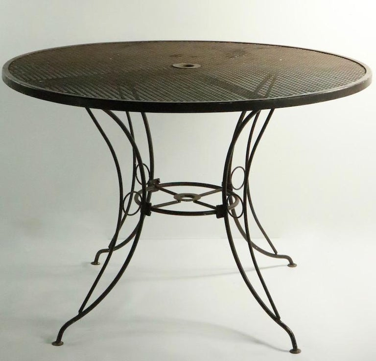 Round wrought iron and metal mesh dining table attributed to Woodard. This table was originally designed for outdoor, poolside, patio, garden use, but is also suitable for interior and or on a porch etc. Currently in later brown paint finish, we