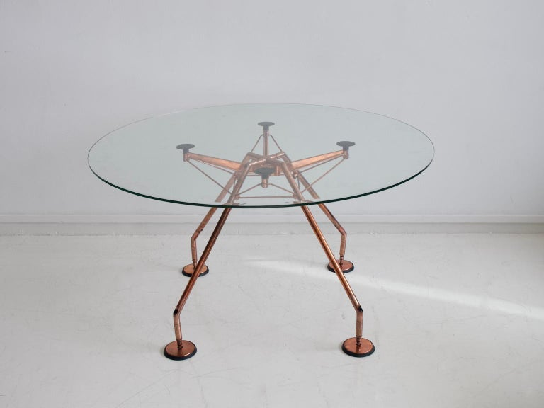 Dining table, model Nomos, design by Sir Norman Foster & Partner for Tecno, Italy. Designed in 1986. Filigree frame made of steel tube and aluminum, which has been renewed and bathed in copper. Loose clear glass plate.