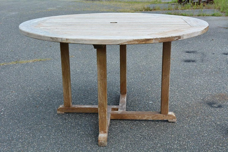 Vintage outdoor round teak wood garden, porch or patio dining table with center hole for umbrella. Measure: 50