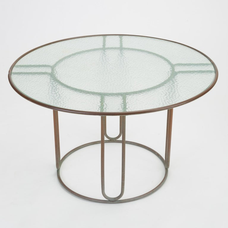 A patio dining table in patinated bronze designed by Walter Lamb and produced by Brown Jordan. The round frame is described by two concentric rings of bronze with radial supports and a circular bronze base. The round tabletop is a single piece of