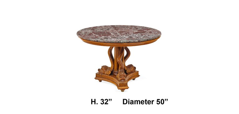 Elegant Italian Neoclassical style round carved walnut three dolphin Pedestal Table with marble top. Early 20th century. A circular purple with white grains marble top is supported by a three intricately hand-carved mythical monopodiae dolphins,