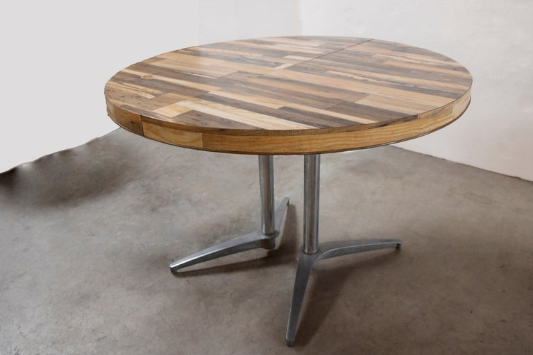 A stand-out, round dining table with metal legs and a thick multi wood grain tabletop. It has a stretcher, making space for a leaf measuring 17 inches in width, extending the table from a perfect circular 41.5 inches diameter to a more oval 58.5