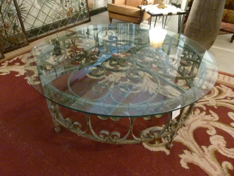 Round recycled coffee table made with a rough iron hand forged base that belonged to a 19th century water well, and a circular form glass on the top. The transparency of the glass allows to see the nice piece below. A combination of antique and