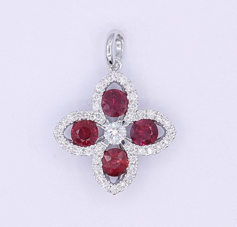 18K White gold pendant featuring four red rubies weighing 0.84 carats flanked with 41 round diamonds weighing 0.24 carats. Color H-I Clarity SI