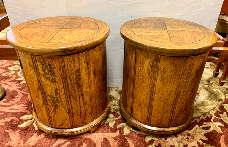 Pair of vintage wood drum end tables features circular top and base, with a single door opening to a storage space without shelving. Perfect flanking a sofa or as nightstands.