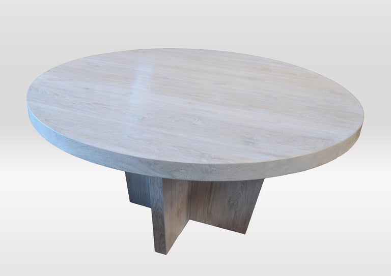 Round reclaimed teak wood dining table with a light white wash finish shown on a modern cross base.  Measures: 60 diameter x 30 high x 2.5 thick.  Andrianna Shamaris. The Leader In Modern Organic Design™.